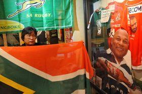 チェスター・ウィリアムズさんの形見となった南アフリカの国旗を広げる加藤丈司さん。右はチェスターさんのパネル=ラグビーダイナーセブンオウス