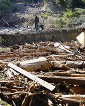 道路が寸断された集落で、土砂や流木の間を歩く住民=15日午後1時7分、宮城県丸森町