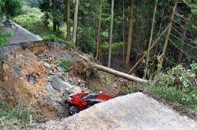 陥没した市道に転落した乗用車=19日午後2時すぎ、福岡県嘉麻市