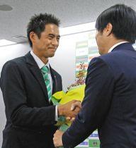会見で望月会長(右)から花束を受け取り、握手する川口選手=相模原市役所で