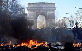パリのシャンゼリゼ大通りで、バリケードを燃やすデモ参加者ら(ゲッティ=共同)