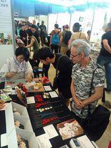 ジャパンエキスポの展示ブースで作業する宮腰さん(左)=宮腰さん提供