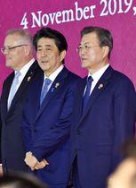 4日、RCEP首脳会合の記念撮影に臨む安倍首相(中央)と韓国の文在寅大統領(右)=バンコク郊外(共同)