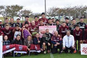 笑顔で集合写真に収まる読谷村関係者とヴィッセル神戸の選手団=27日、読谷村のZANPAプレミアム残波岬ボールパーク