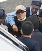 大阪市東住吉区の路上で、茨城県警の捜査員らに確保される宮崎文夫容疑者=18日午前(近隣住民提供)