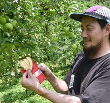 リンゴ畑で「アップルトリップ」を手にする宮下さん
