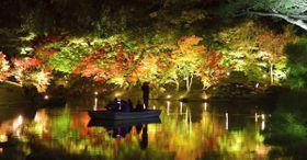 試験点灯で湖面に鮮やかに映し出された紅葉=香川県高松市栗林町