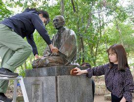 玉楮象谷の銅像をたわしで丁寧に清掃する県漆芸研究所の研究生ら=香川県高松市番町、市中央公園