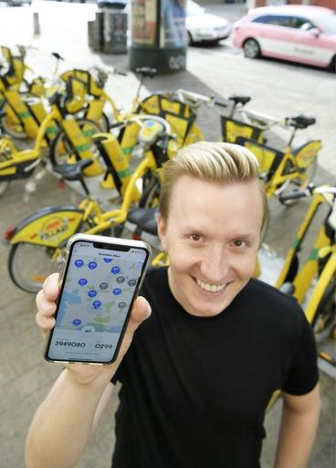 スマホアプリ「ウィム」で通勤方法を決めるハッリ・ニーミネン。この日は自転車を使った=19年8月、ヘルシンキ(共同)