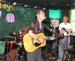2周年記念イベントに向けてステージで練習する出演者を見守る脇村さん(右)