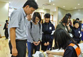 東海村からつくばみらい市の施設に到着した小学生と迎えの保護者ら=同市で