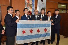 シカゴ市から贈られた市旗を手に、記念撮影する林会長(左端)、小野寺市長(左から3人目)ら