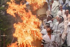 参道を練り歩く燃え盛る大たいまつを持った男たち(和歌山県那智勝浦町で)