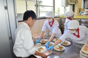 調理服姿で作った給食を配膳する食物調理科の生徒