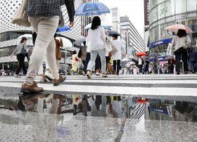 長袖シャツ姿で傘を手に行き交う人たち。天気がぐずつき、初夏とは思えない涼しい日々が続く=16日午後、東京・銀座