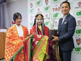 【鈴木知事(右)にハナショウブを手渡す橋本さん(中央)と北岡さん=三重県庁で】