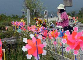 夏の大祭が始まったむつ市の恐山。風車が回る中、参拝者が亡き人の面影をしのび手を合わせた=20日午前10時ごろ