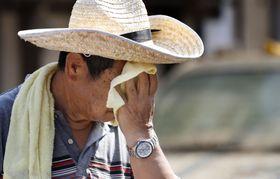 岡山県倉敷市真備町地区で、片付けの合間に汗を拭う男性=15日午前9時22分