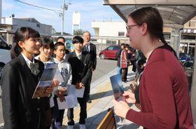 外国人観光客に英語で話し掛ける小豆島中央高生ら=香川県土庄町、土庄港