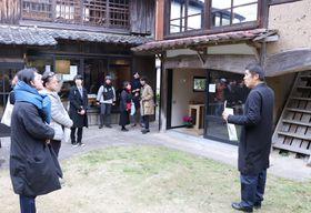 空き家を生かしたまちづくりについて城谷さん(右)の説明を聞く参加者=雲仙市小浜町