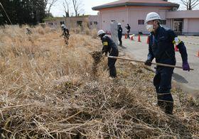 復興拠点で除染を行う作業員=14日午前、福島県大熊町