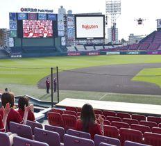 ドローン(右上)で撮影し、映し出された高画質映像(左上の大型ビジョン)=15日午後、仙台市の野球場「楽天生命パーク宮城」