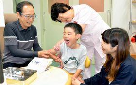 「はい、ちょっと我慢して」。向田隆通院長(左)のもと、元気に再接種を受ける宮内理久斗君(中)と母仁美さん(右)=6月、むかいだ小児科