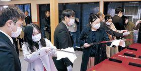 日本刀を手に取り、感触を確かめる来場者=津幡町の倶利迦羅不動寺山頂本堂
