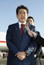 シンガポールへの出発を前に記者団の取材に応じる安倍首相=14日午前、羽田空港