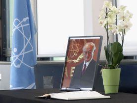 22日、天野之弥事務局長の死を悼みIAEA本部に設置された遺影と記帳台=ウィーン(共同)