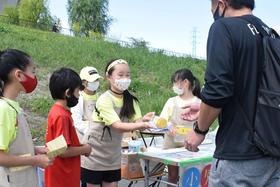 来場者にレモネードを手渡す谷川ほずみさん(中央)=18日午後、さいたま市緑区