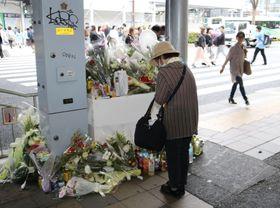 神戸市営バス事故の現場近くに設置された献花台で手を合わせる女性=23日午後、神戸市