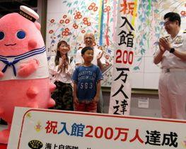 200万人目の入館者となり、祝福を受ける烏山君(中央)=佐世保市、セイルタワー