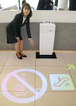 三菱電機が発表した道案内システム「てらすガイド」。プロジェクター(奥)から床に動く絵文字を投影させて案内を表示する=18日、東京都中央区