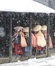 雪が降る中、雁木通りを歩く瞽女役の一行=10日、上越市大町5