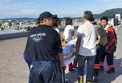 被災した「まび記念病院」の屋上に患者を運び、ヘリコプターによる救出を待つ稲葉基高医師(右端)ら=2018年7月8日、岡山県倉敷市(ピースウィンズ・ジャパン提供)