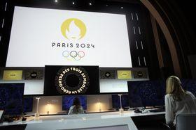 発表イベント会場のスクリーンに映し出された2024年パリ五輪のロゴ=21日、パリ(AP=共同)