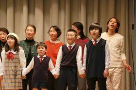 「取手市民のうた〜新しい明日〜」のレコーディングでコーラス参加者と一緒に歌う歌手の谷本貴義さん(右端)=同市藤代(同市提供)
