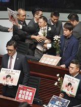 香港立法会の本会議で抗議し、保安要員に連れ出される民主派議員(上中央)ら=17日(共同)