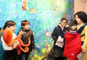 水槽に見立てた工作の前で、来場者にタコの特徴を説明する児童(左端)