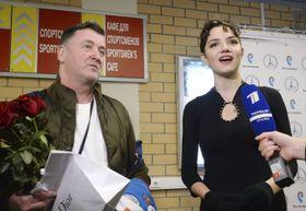 新シーズンのフリー演技公開後、記者の質問に答えるフィギュアスケート女子のエフゲニア・メドベージェワ選手。左はブライアン・オーサー・コーチ=9日、モスクワ(共同)