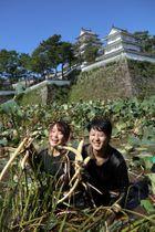 掘り出したレンコンを掲げる参加者=島原城