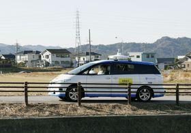 遠隔型自動運転システムの実証実験で、運転席に人を乗せずに公道を走る乗用車=14日午前、愛知県幸田町