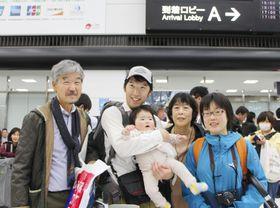 成田空港に帰国し、長女を抱く西山尚典隊員と家族=21日午後