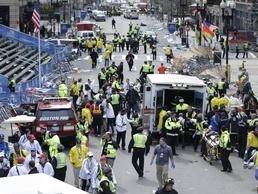 2013年のボストン・マラソンのゴール付近で、爆発によるけが人を救助する医療関係者ら(AP=共同)