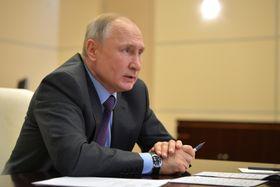 3日、モスクワ郊外の公邸で原油価格を巡る閣僚らとのテレビ会議に参加したロシアのプーチン大統領(タス=共同)