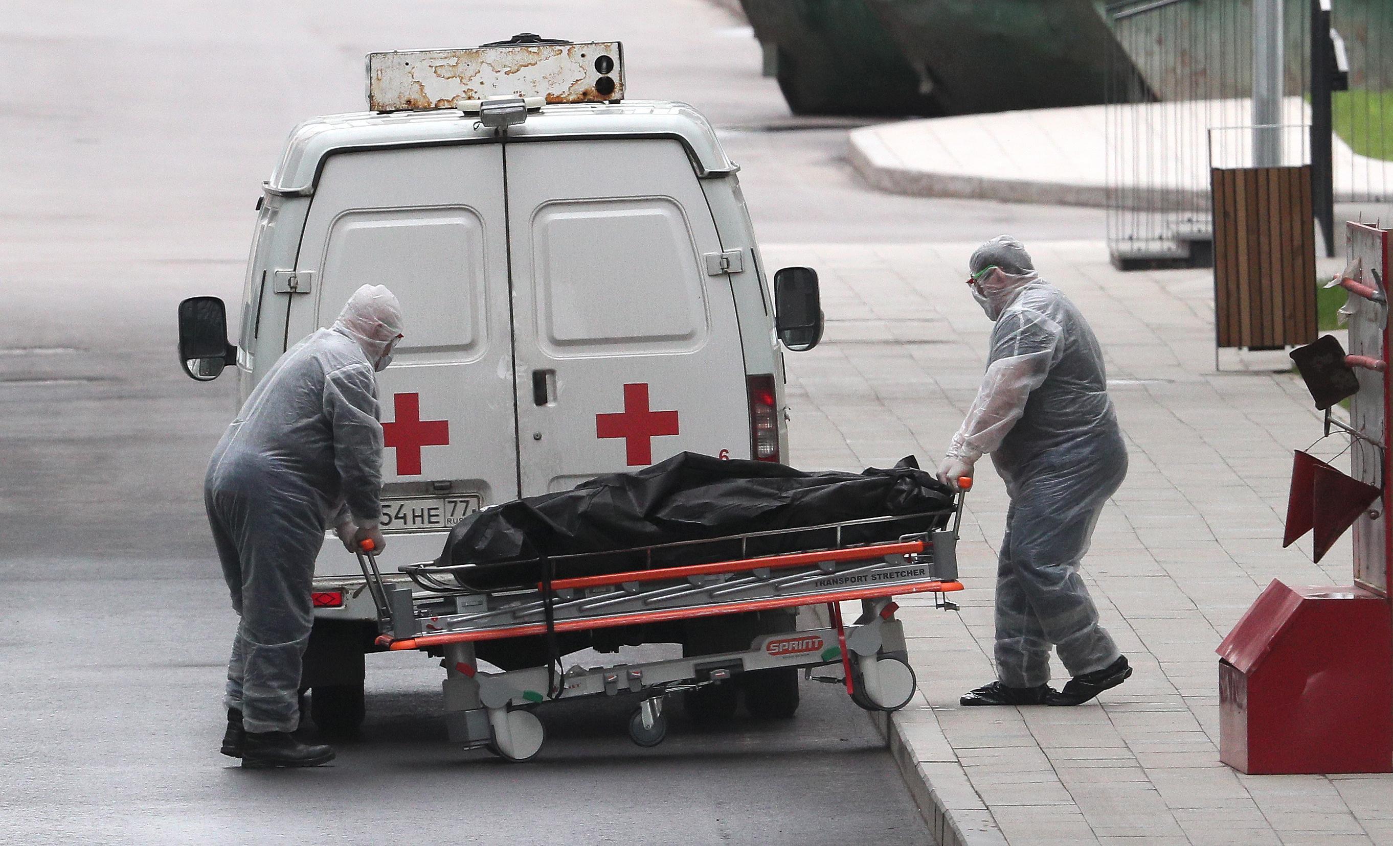 死亡した患者を運ぶ医療関係者=25日、モスクワ(タス=共同)