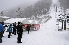 時折ふぶく中、リフトの始動を確認し、拍手を送る地元関係者ら(京丹後市弥栄町野中・スイス村スキー場)