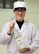日本酒「萩の鶴 メガネ専用」を手に笑顔の佐藤曜平さん=11月、宮城県栗原市
