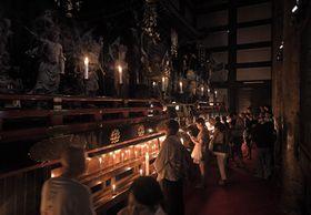 ろうそくの明かりに照らし出された内々陣を巡り、手を合わせる参拝者ら(9日午後2時30分、京都市東山区・清水寺)